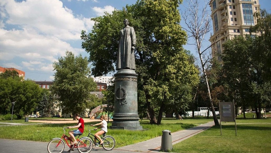 People cycle past a statue of Felix Dzerzhinsky, the founder of the Soviet secret police, in the Museon Park, also known as Fallen Monument Park, in Moscow, Russia, Wednesday, June 24, 2015. The Moscow city legislature has agreed to allow residents to decide whether the statue of Felix Dzerzhinsky should be restored to a square in central Moscow. The statue of the Bolshevik revolutionary known as Iron Felix stood outside KGB headquarters in Moscow until it was toppled by protesters in 1991 in the final months of the Soviet Union. (AP Photo/Alexander Zemlianichenko)