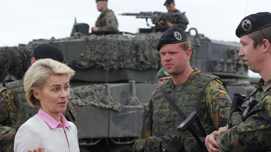 German Defence Minister Ursula von der Leyen speaks with German soldiers after the NATO Noble Jump exercise on a training range near Swietoszow Zagan, Poland, Thursday, June 18, 2015. (AP Photo/Alik Keplicz)