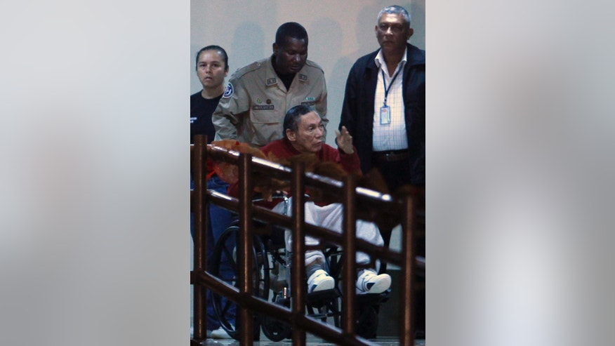 FILE - In this Dec. 11, 2011, file photo, Panama's ex-dictator Manuel Noriega gestures while being carried in a wheelchair by a police officer inside El Renacer prison in the outskirts of Panama City. Speaking to local television network the former Panamanian strongman broke his long silence in a interview from jail, aired on Wednesday, June 24, 2015, asking his compatriots to forgive actions by the military that culminated in the 1989 American invasion. (AP Photo/Esteban Felix, File)
