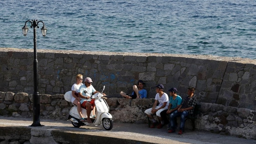 In this photo taken on Tuesday, June 16, 2015 tourists with a scooter pass by Afghan migrants, at the port of Molyvos, also known by its official name Mithymna, on the northeastern Greek island of Lesbos. More than 25,000 migrants have arrived this year in Greece's third largest island as many locals and officials say the crisis has not yet severely impacted the island's lucrative tourist industry, a major source of income, and visitors have shown compassion and understanding. (AP Photo/Thanassis Stavrakis)