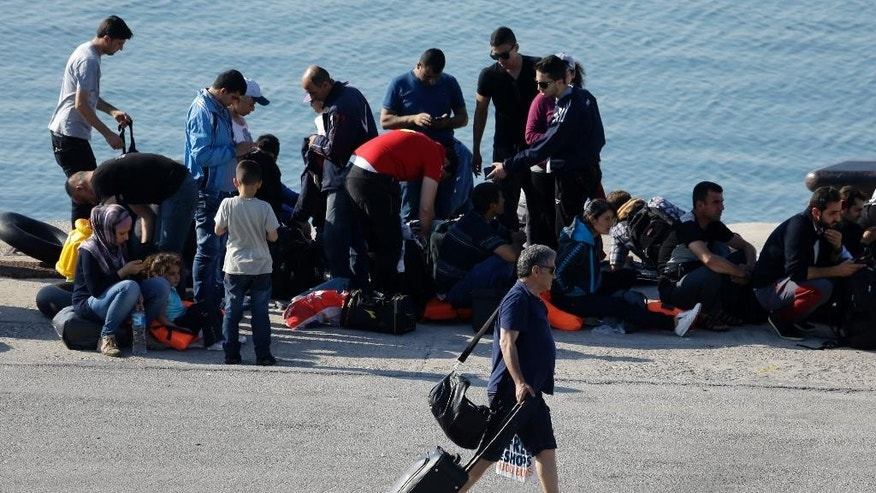 In this photo taken on Wednesday, June 17, 2015 a tourist walks past migrants at the port of Mytilene, on the northeastern Greek island of Lesbos. More than 25,000 migrants have arrived this year in Greece's third largest island as many locals and officials say the crisis has not yet severely impacted the island's lucrative tourist industry, a major source of income, and visitors have shown compassion and understanding. (AP Photo/Thanassis Stavrakis)