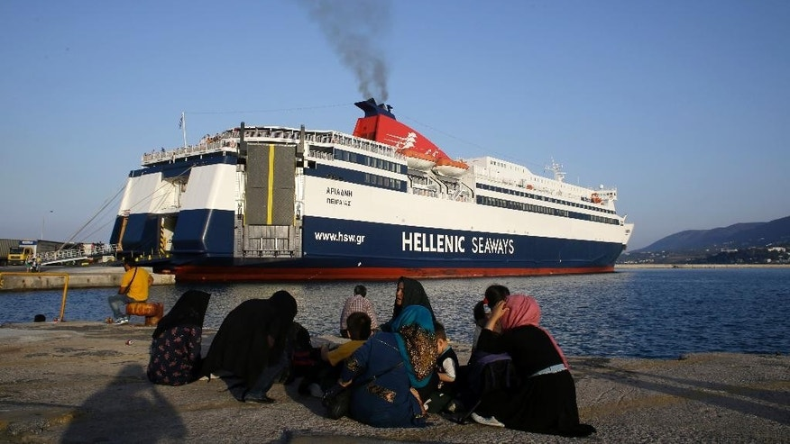In this photo taken on Tuesday, June 16, 2015 migrants sit at the port of Mytiline, on the northeastern Greek island of Lesbos as a ferry prepares for departure to Athens' port of Piraeus. About 25,000 migrants have arrived this year in Greece's third largest island as many locals and officials say the crisis has not yet severely impacted the island's lucrative tourist industry, a major source of income, and visitors have shown compassion and understanding. (AP Photo/Thanassis Stavrakis)