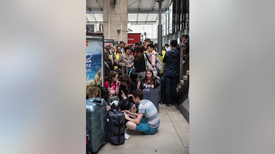 Passengers wait stranded as Eurostar trains are canceled at Gare du Nord station in Paris, Tuesday, June 23, 2015. Train and ferry services from the northern French city of Calais to Britain were cut off Tuesday by striking port workers, stranding hundreds of trucks and thousands of passengers on both sides of the English Channel. Adding to the chaos, illegal migrants camped by the thousands in the port city were seen trying to stowaway on vehicles stuck in traffic jams. (AP Photo/Kamil Zihnioglu)