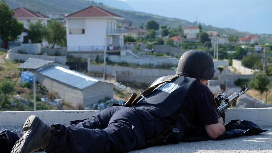 An Albanian police officer takes position on the rooftop of a house during an operation at the village of Lazarat, about 200 kilometers (125 miles) south of Tirana, Wednesday, June 24, 2015. Dozens of Albanian police, backed up by two army helicopters, have been deployed to a major illegal marijuana-growing village after gunmen fatally shot one policeman and wounded two others on Wednesday. (AP Photo/Hektor Pustina)