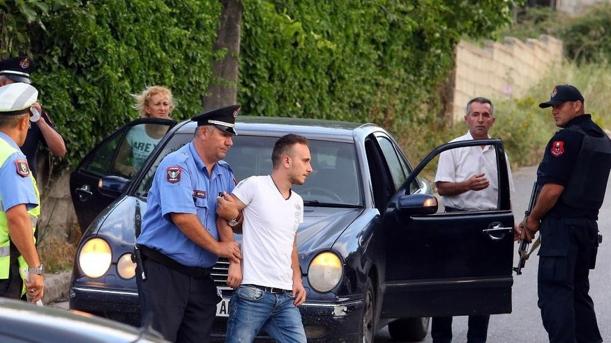 Albanian police detain a man during an operation in the village of Lazarat, about 200 kilometers (125 miles) south of Tirana, Wednesday, June 24, 2015. Dozens of Albanian police, backed up by two army helicopters, have been deployed to a major illegal marijuana-growing village after gunmen fatally shot one policeman and wounded two others on Wednesday. (AP Photo/Hektor Pustina)