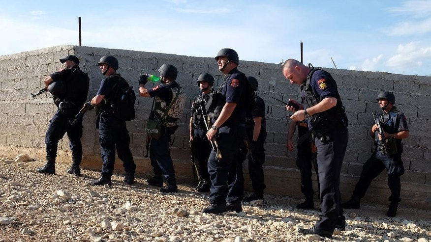 Albanian police forces operate at the village of Lazarat, about 200 kilometers (125 miles) south of Tirana, Wednesday, June 24, 2015. Dozens of Albanian police, backed up by two army helicopters, have been deployed to a major illegal marijuana-growing village after gunmen fatally shot one policeman and wounded two others on Wednesday. (AP Photo/Hektor Pustina)