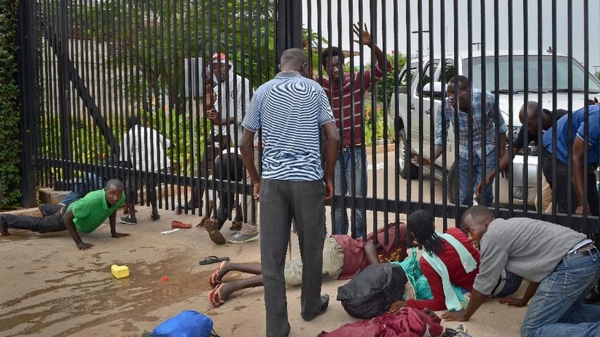 Student protesters seeking refuge crawl under the gates of the U.S. Embassy in the capital Bujumbura, Burundi Thursday, June 25, 2015. The U.S Embassy in Burundi says about 100 university students are in the embassy's parking lot seeking refuge, after police persuaded the students to move from an adjacent construction site where they had camped out after the government closed their university due to the political turmoil. (AP Photo)