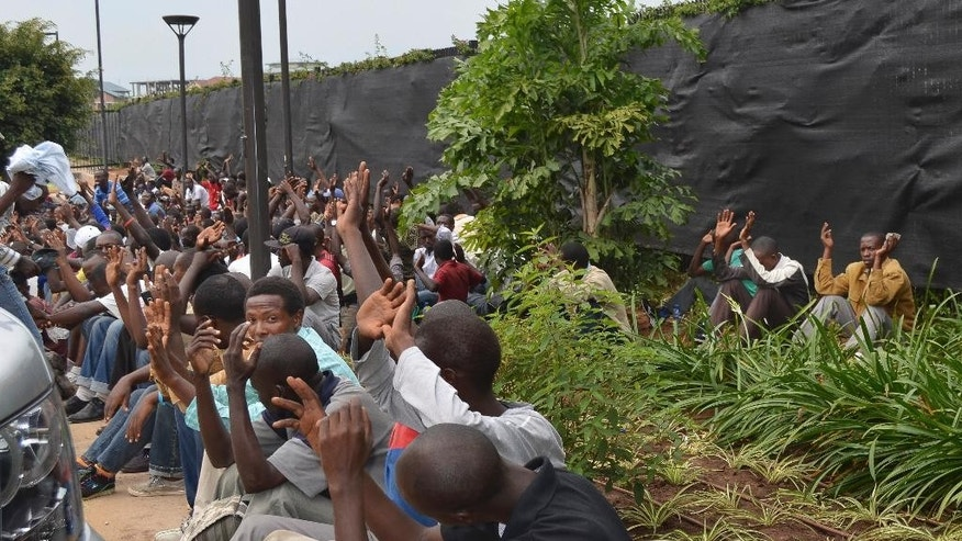 Student protesters sit on the ground with their hands up in the air, inside the embassy parking lot, after crawling under the gates at the U.S. Embassy in the capital Bujumbura, Burundi Thursday, June 25, 2015. The U.S Embassy in Burundi says about 100 university students are in the embassy's parking lot seeking refuge, after police persuaded the students to move from an adjacent construction site where they had camped out after the government closed their university due to the political turmoil. (AP Photo)
