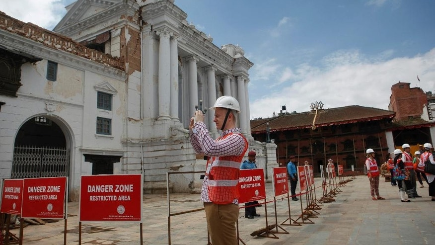 A foreign delegate photographs damaged buildings at the Basantapur Durbar Square heritage site in Kathmandu, Nepal, Wednesday, June 24, 2015. Delegates representing some 53 nations, donor agencies and development partners will attend the International Donors' Conference on Nepal's Reconstruction on Thursday, June 25, to help Nepal rebuild after powerful earthquakes shook the Himalayan nation in April and May and took more than 8,700 lives. (AP Photo/Niranjan Shrestha)