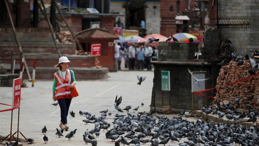 A foreign delegate walks at the Basantapur Durbar Square heritage site in Kathmandu, Nepal, Wednesday, June 24, 2015. Delegates representing some 53 nations, donor agencies and development partners will attend the International Donors' Conference on Nepal's Reconstruction on Thursday, June 25, to help Nepal rebuild after powerful earthquakes shook the Himalayan nation in April and May and took more than 8,700 lives. (AP Photo/Niranjan Shrestha)