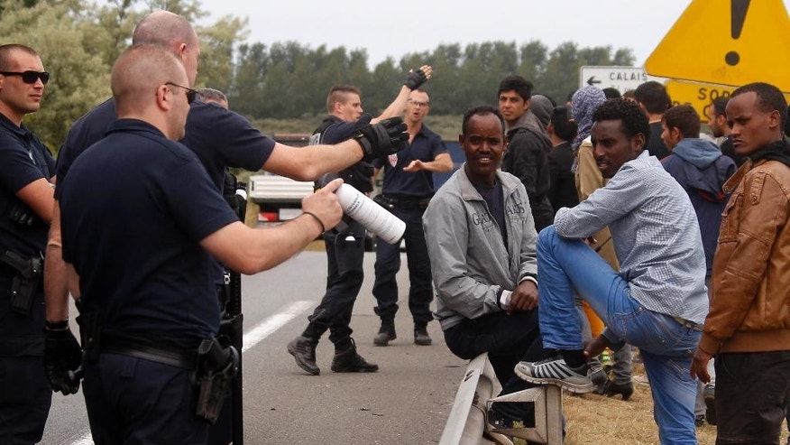 French police officers stand guard on the motorway leading to the ferry port to cross the English Channel, in Calais, northern France, Thursday, June 25, 2015. Migrants from Sudan, Eritrea and elsewhere are camped by the thousand in the port city of Calais trying to reach Britain, where they believe they will have better job prospects. (AP Photo/Michel Spingler)