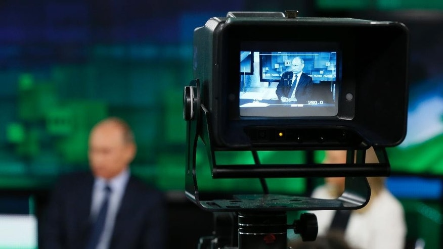 "FILE - In this Tuesday, June 11, 2013 file photo, Russian President Vladimir Putin is shown on the screen of a camera viewfinder at the new headquarters of ""Russia Today"" television channel in Moscow, Russia. Major brands in the export division of Russian media include RT, the RIA Novosti news agency and its English-language arm Sputnik, and the Voice of Russia radio station. Despite the pounding Russia's economy is taking from the slump in the price of crude oil and the West's Ukraine-related sanctions, the annual government budget allocation for RT alone has been hiked by 30 percent since 2014, to the ruble equivalent of $289 million. (Yuri Kochetkov/Pool Photo via AP, File)"