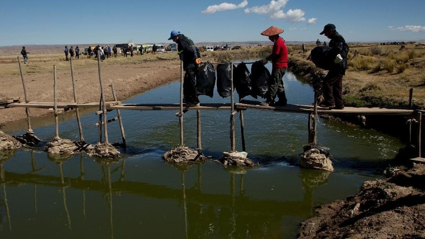 This June 20, 2015 photo shows volunteers carrying bags of plastic bottles they collected from the Katari River that feeds into Lake Titicaca in Bahia de Cohana, Bolivia. Most pollution on the Bolivian side, including such toxic heavy metals as lead and arsenic, originates in El Alto, a fast-growing city near La Paz that sits above the lake. (AP Photo/Juan Karita)