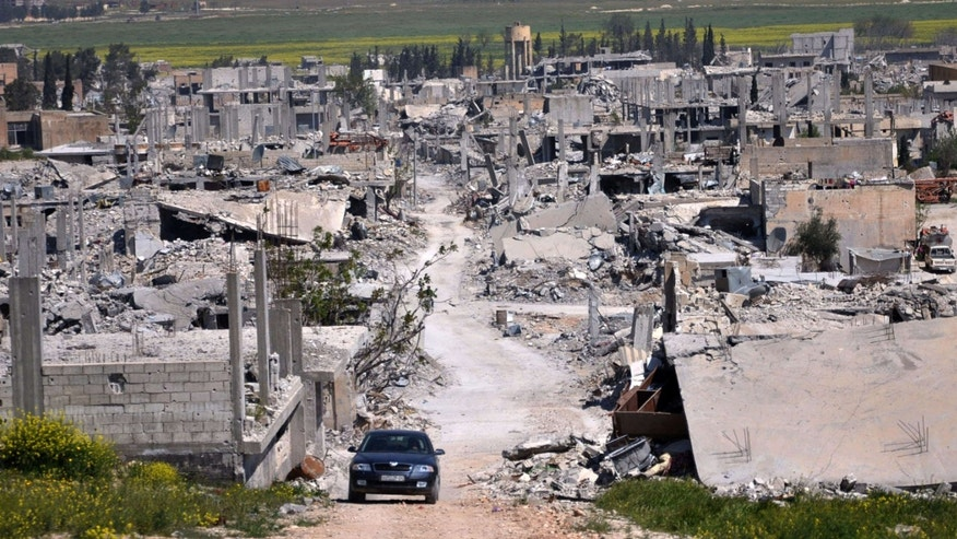 April 18, 2015: A car passes in an area that was destroyed during the battle between the U.S. backed Kurdish forces and the Islamic State fighters, in Kobani, north Syria.