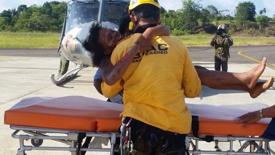 In this photo distributed by Colombia's Air Force, a rescue worker puts Maria Nelly Murillo on a stretcher after she and her baby were airlifted for medical treatment to Quibdo, in Colombia's western state of Choco, Wednesday, June 24, 2015. Rescuers reached Murillo and her 1-year-old son after they survived a June 20 plane crash in the jungle, shortly after taking off from Quibdo. The pilot was killed, and Murillo suffered some injuries and burns, but the baby was unhurt. (Colombia's Air Force via AP)