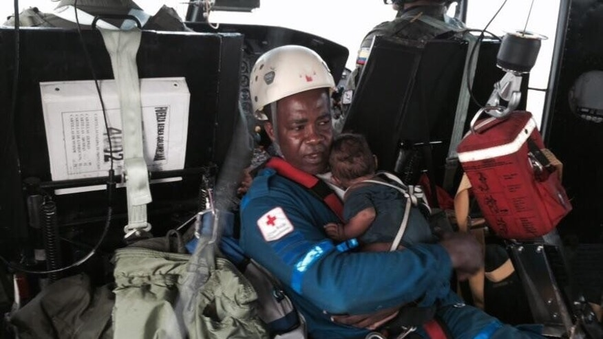 In this photo distributed by Colombia's Air Force, a Colombian Red Cross volunteer holds one-year-old Yudier Moreno as he and his mother are flown by helicopter for medical treatment to Quibdo, in Colombia's western state of Choco, Wednesday, June 24, 2015. Rescuers reached the baby and his mother after they survived a June 20 plane crash in the jungle shortly after taking off from Quibdo. The pilot was killed, and the mother suffered some injuries and burns, but the baby was unhurt. (Colombia's Air Force via AP)