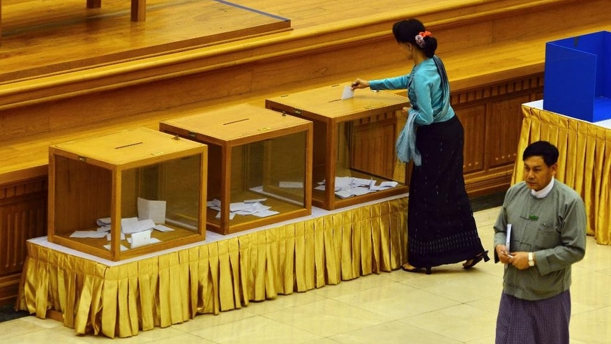 Myanmar's opposition leader Aung San Suu Kyi casts her vote for constitution amendments during a regular session at the Union Parliament Thursday, June 25, 2015, in Naypyitaw, Myanmar. Myanmar's parliament has voted against constitutional amendments Thursday, ensuring that the military's veto power remains intact and that Suu Kyi cannot become president in an election this year. (AP Photo/Aung Shine Oo)