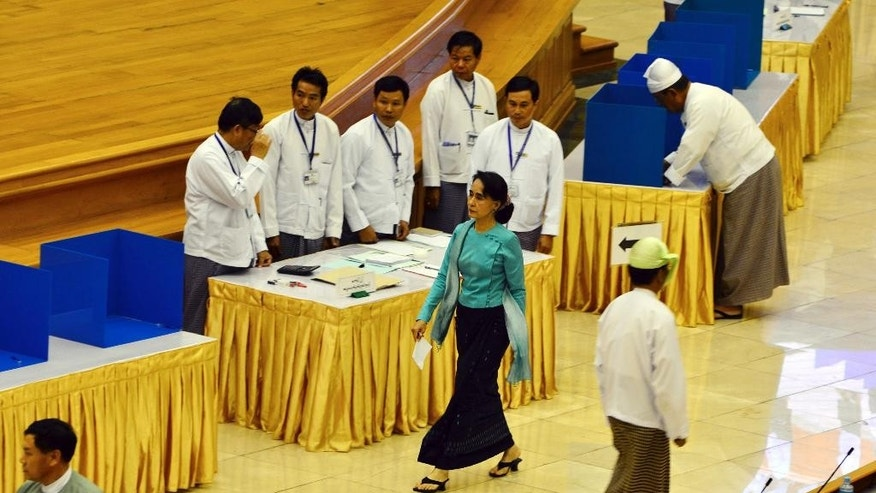 Myanmar's opposition leader Aung San Suu Kyi, center, walks to cast her vote for constitution amendments during a regular session at the Union Parliament Thursday, June 25, 2015, in Naypyitaw, Myanmar. Myanmar's parliament has voted against constitutional amendments Thursday, ensuring that the military's veto power remains intact and that Suu Kyi cannot become president in an election this year. (AP Photo/Aung Shine Oo)