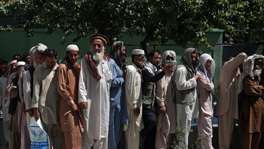 Afghan men wait in line to receive food donation during the holy month of Ramadan in Kabul, Afghanistan, Thursday, June 25, 2015. Muslims throughout the world are marking the month of Ramadan, the holiest month in the Islamic calendar during which devotees fast from dawn till dusk. (AP Photo/Massoud Hossaini)