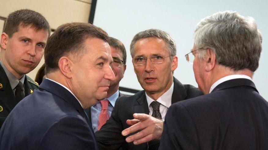 NATO Secretary General Jens Stoltenberg, second right, speaks with Ukraine's Defense Minister Stepan Poltorak, second left, during a meeting of the NATO-Ukraine Commission at NATO headquarters in Brussels on Thursday, June 25, 2015. NATO defense ministers meet for a second day of sessions to discuss, among other issues, the situation in Ukraine. (AP Photo/Virginia Mayo)