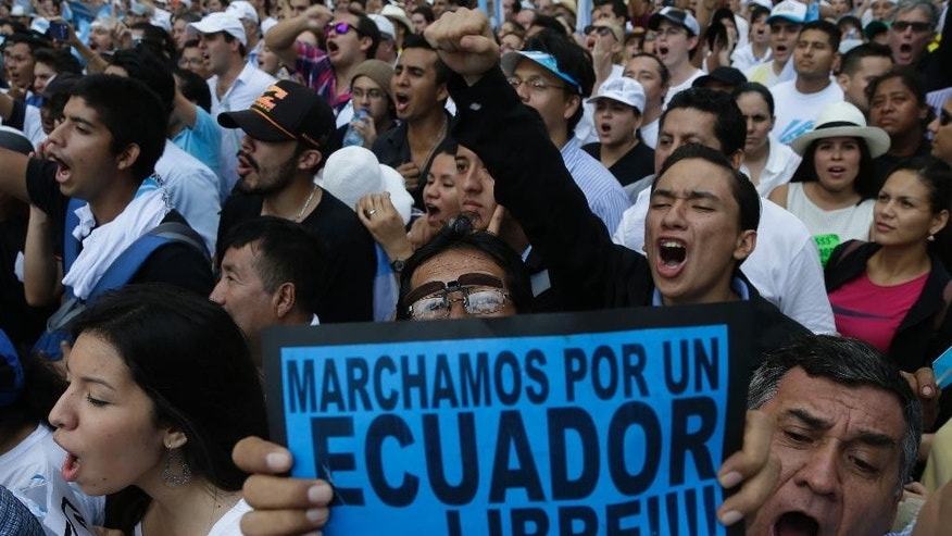 "Demonstrators hold a sign that reads in Spanish ""We march for a free Ecuador"" during an opposition march called by Guayaquil's mayor Jaime Nebot to protest against policies of President Rafael Correa in Guayaquil, Ecuador, Thursday, June 25, 2015. Speaking to a crowd stretching in to the distance, Nebot said the president's economic policies are harmful and threaten to throw the country into turmoil. (AP Photo/Dolores Ochoa)"