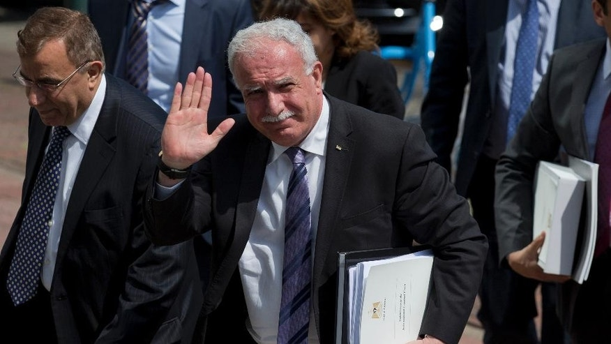 Palestinian Foreign Minister Riyad Al-Maliki waves as he arrives holding documents he will submit to the International Criminal Court in The Hague, Netherlands, Thursday, June 25, 2015. The Palestinian foreign minister is visiting the International Criminal Court to hand prosecutors files detailing possible Israeli war crimes in Gaza and settlement construction in the West Bank and East Jerusalem. (AP Photo/Peter Dejong)
