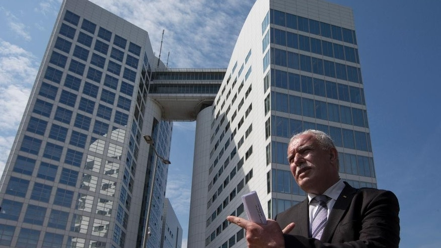 Palestinian Foreign Minister Riyad Al-Maliki waits to give an interview outside the International Criminal Court, rear, in The Hague, Netherlands, Thursday, June 25, 2015. The Palestinian foreign minister visited the International Criminal Court to hand prosecutors files detailing possible Israeli war crimes in Gaza and settlement construction in the West Bank and East Jerusalem. (AP Photo/Peter Dejong)