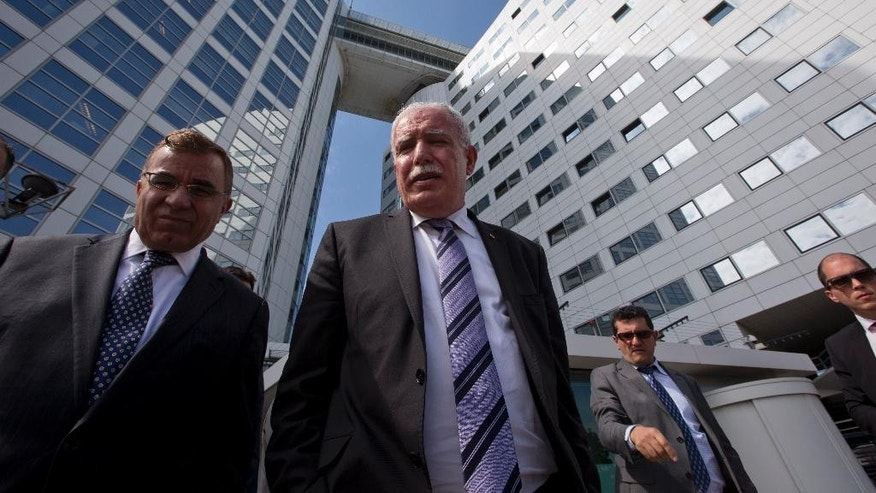 Palestinian Foreign Minister Riyad Al-Maliki, center, waits on the steps of the International Criminal Court after answering questions of reporters in The Hague, Netherlands, Thursday, June 25, 2015. The Palestinian foreign minister visited the International Criminal Court to hand prosecutors files detailing possible Israeli war crimes in Gaza and settlement construction in the West Bank and East Jerusalem. (AP Photo/Peter Dejong)