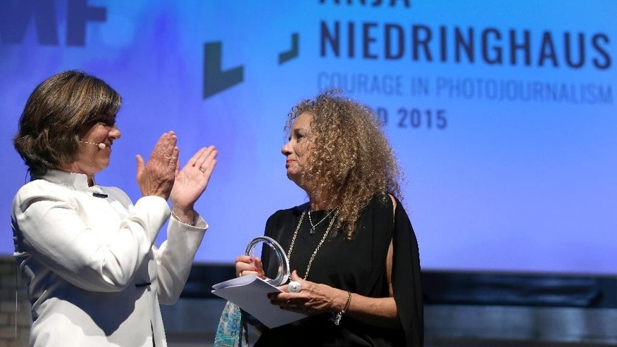 CNN journalist Christiane Amanpour, left, applauds after she handed over the 2015 Anja Niedringhaus Award to photographer Heidi Levine, right, in Berlin, Germany, Thursday, June 25, 2015. The Anja Niedringhaus Courage in Photojournalism Award was created to honor the life and work of Pulitzer Prize-winning AP photographer Anja Niedringhaus (1965-2014). (AP Photo/Michael Sohn)