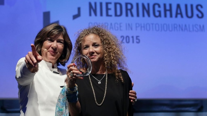 CNN journalist Christiane Amanpour, left, hands over the 2015 Anja Niedringhaus Award to photographer Heidi Levine, right, in Berlin, Germany, Thursday, June 25, 2015. The Anja Niedringhaus Courage in Photojournalism Award was created to honor the life and work of Pulitzer Prize-winning AP photographer Anja Niedringhaus (1965-2014). (AP Photo/Michael Sohn)