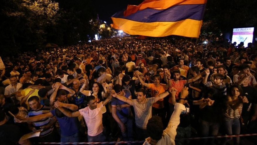 Armenian protesters dance while waving a national flag during a protest rally against a hike in electricity prices in Yerevan, Armenia, Wednesday, June 24, 2015. A standoff between police and demonstrators protesting a hike in electricity prices blocked the central avenue in the Armenia capital on Wednesday for the third day running. (Hrant Khachatryan/PAN Photo via AP)