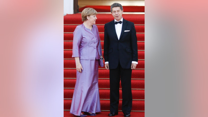 German Chancellor Angela Markel, left, and her husband Joachim Sauer arrive for an official state dinner for Britain's Queen Elizabeth II, in front of Germany's President Joachim Gauck's residence Bellevue Palace in Berlin, Wednesday, June 24, 2015. Queen Elizabeth II and her husband Prince Philip are on an official visit to Germany until Friday, June 26. (AP Photo/Markus Schreiber)