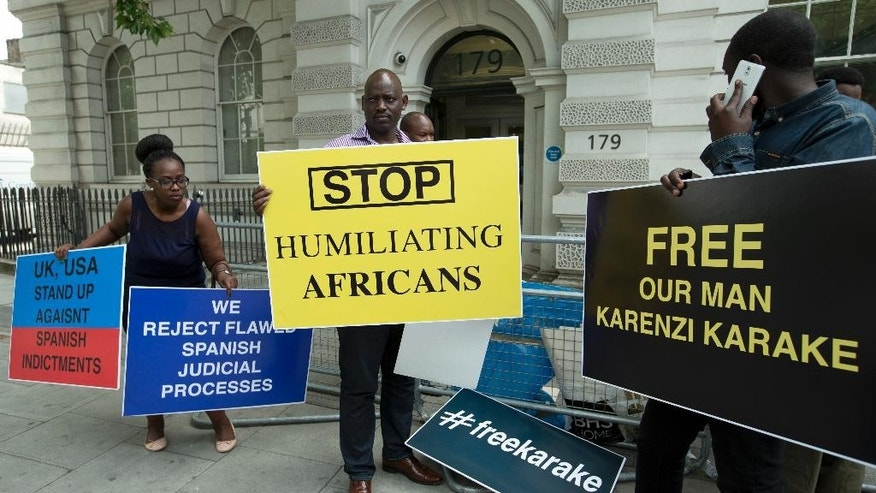 Supporters of  Karenzi Karake, the Rwandan intelligence chief, hold placards outside Westminster Magistrates Court in London, where he is due to appear, Thursday, June 25, 2015.  Karenzi Karake, a Rwandan national, is set appear before Westminster Magistrates' Court Thursday after being arrested Saturday, June 20 on a European Arrest Warrant on behalf of the authorities in Spain, where he is wanted in connection with war crimes against civilians. (AP Photo/Alastair Grant)