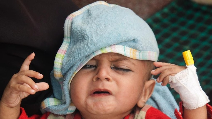 A Pakistani child who is suffering from dehydration due to extreme weather admitted at a local hospital in Karachi, Pakistan, Thursday, June 25, 2015. The devastating heat wave that struck southern Pakistan last weekend is slowly subsiding but the toll was still climbing Thursday, a senior health official said. (AP Photo/Shakil Adil)