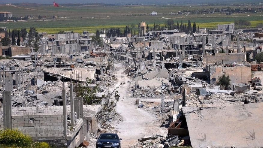 FILE - In this picture taken on Saturday, April 18, 2015, a car passes in an area that was destroyed during the battle between the U.S. backed Kurdish forces and the Islamic State fighters, in Kobani, north Syria. Turkish officials said on Thursday, June 25, 2015 that the Islamic State group has staged a new attack on the Kurdish town of Kobani, which resisted a months-long assault by the Islamic militants until they were pushed out earlier this year. Two Turkish officials say Thursday's attack involved a suicide bomber detonating his car near the border gate. (AP Photo/Mehmet Shakir, File)