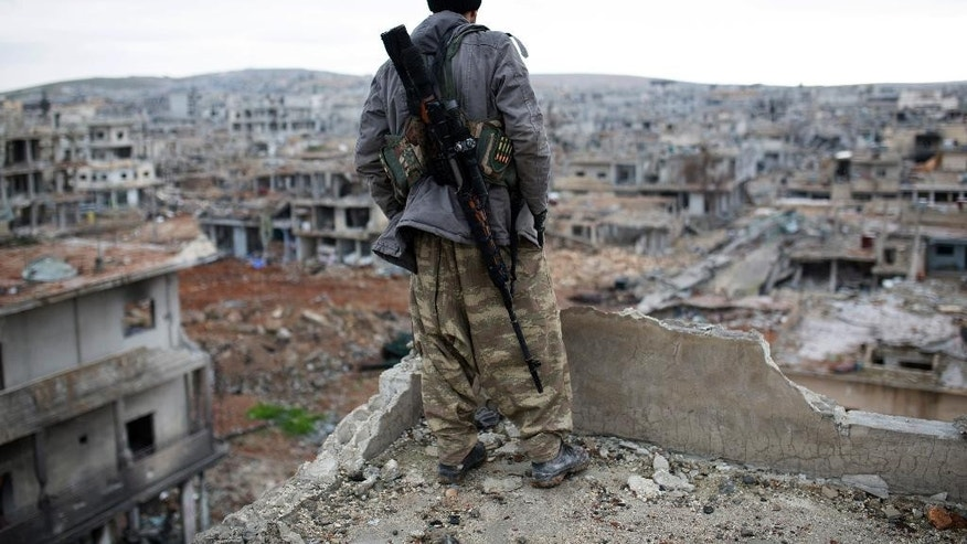 FILE - In this Jan. 30, 2015 file photo, a Syrian Kurdish sniper looks at the rubble in the Syrian city of Ain al-Arab, also known as Kobani. Turkish officials said on Thursday, June 25, 2015 that the Islamic State group has staged a new attack on the Kurdish town of Kobani, which resisted a months-long assault by the Islamic militants until they were pushed out earlier this year. Two Turkish officials say Thursday's attack involved a suicide bomber detonating his car near the border gate. (AP Photo, File)