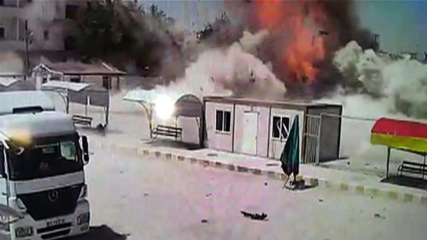 In this still image taken from video captured on a CCTV camera, made available Thursday, June 25, 2015, an explosion is captured by a camera on the Turkish side of the border, moments after a car bomb detonates in the town of Kobani, Syria. Islamic State militants staged a new attack on the Kurdish town of Kobani, which famously resisted a months-long assault by the Islamic militants. The attack involved a suicide car bombing that wounded scores. (AP Photo)