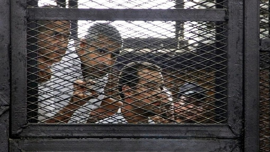 FILE - In this Monday, June 23, 2014, file photo, from left, Australian correspondent Peter Greste, Canadian-Egyptian acting bureau chief of Al-Jazeera Mohamed Fahmy, and Egyptian producer Baher Mohammed, appear in a defendant's cage in a courtroom in Cairo, Egypt. A watchdog group says journalists face unprecedented threats in President Abdel-Fattah el-Sissi's Egypt, with the highest number behind bars since its records started in 1990. (AP Photo/Heba Elkholy, El Shorouk Newspaper, File) EGYPT OUT