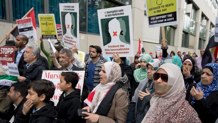 FILE - In this Sunday, June 21, 2015, file photo, people attend a protest rally in front of a court to support the release of the journalist Ahmed Mansour in Berlin, Germany. Ahmed Mansour, 52, a senior journalist with the Qatar-based broadcaster Al-Jazeera, was detained at Tegel airport on Saturday on an Egyptian arrest warrant. A watchdog group says journalists face unprecedented threats in President Abdel-Fattah el-Sissi's Egypt, with the highest number behind bars since its records started in 1990. (AP Photo/Michael Sohn, File)