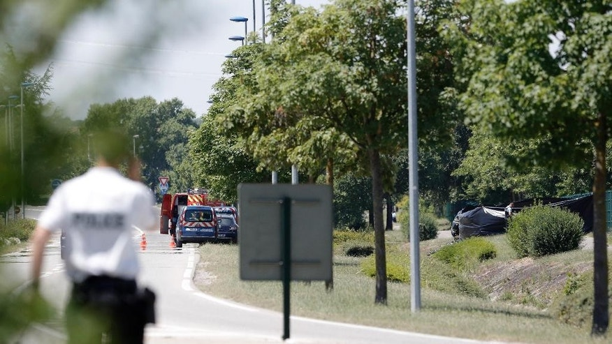 A police officers park outside the plant where an attack took place, Friday, June 26, 2015 in Saint-Quentin-Fallavier, southeast of Lyon, France. French authorities say one person has been beheaded in an attack and explosion at a gas factory in the southeastern part of the country. Officials say banners with Arabic writing were found near the body. Authorities have opened a terrorism investigation. (AP Photo/Laurent Cipriani)