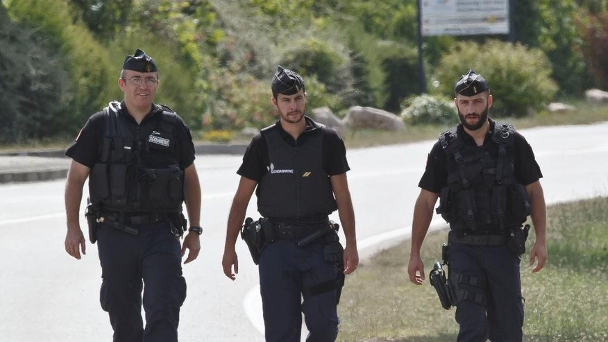 Police officers walk along the road leading to a plant where an attack took place in Saint-Quentin-Fallavier, southeast of Lyon, France, Friday, June 26, 2015. A man with suspected ties to French Islamic radicals rammed a car Friday into an American gas factory in southeastern France, triggering an explosion that injured some people, officials said. The severed head of a local businessman was left hanging at the factory's entrance, along with banners with Arabic inscriptions, they said. (AP Photo/Michel Euler)