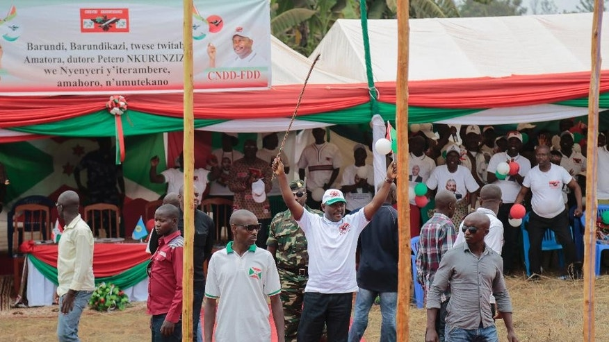 Surrounded by bodyguards, Burundian President Pierre Nkurunziza, waves to the crowd during presidential campaigning Friday June 26, 2015, in Giteranyi, Muyinga, Burundi.  Burundi has experienced weeks of unrest since the ruling party's April 26th announcement that President Pierre Nkurunziza will run for a third term in office. (AP Photo/Gildas Ngingo)