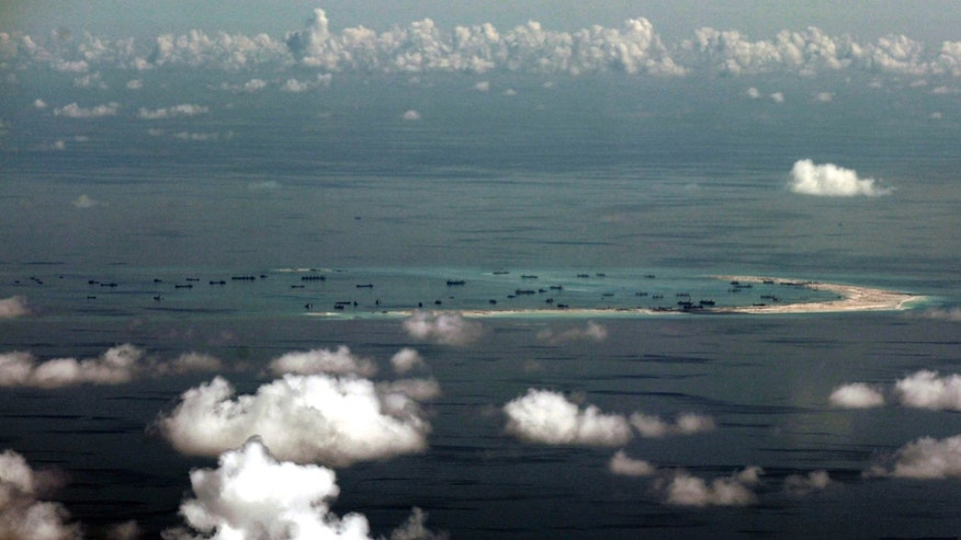 May 11, 2015: This aerial photo taken through a glass window of a military plane shows China's alleged on-going reclamation of Mischief Reef in the Spratly Islands in the South China Sea.
