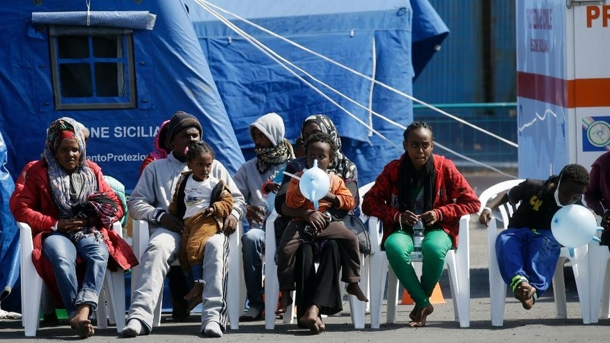 Migrants wait near a red cross tent after disembarking from the Belgian Navy Vessel Godetia at the Trapani harbor, Sicily, Italy, Wednesday, June 24, 2015. Hundreds of migrants were rescued Tuesday by the Godetia Belgian Navy Vessel, part of a EU Navy Vessels fleet taking part in the Triton migrants rescue operations. (AP Photo/Gregorio Borgia)