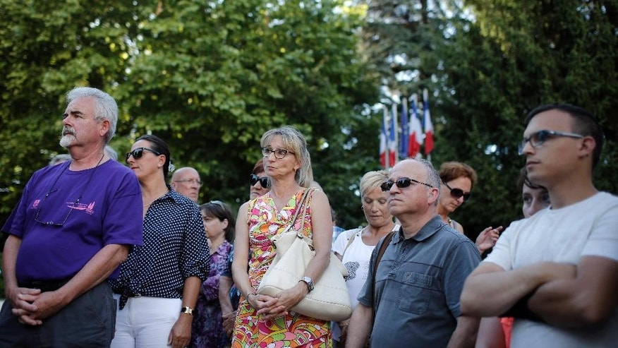 People gather in Bourgoin, southeast of Lyon, France, to pay their respects to the victim of the attack which took place earlier in Saint-Quentin-Fallavier, Friday, June 26, 2015. A man with suspected ties to French Islamic radicals rammed a car Friday into an American gas factory in southeastern France, triggering an explosion that caused injuries, officials said. The severed head of a local businessman was left hanging at the factory's entrance, along with banners with Arabic inscriptions, they said. (AP Photo/Laurent Cipriani)