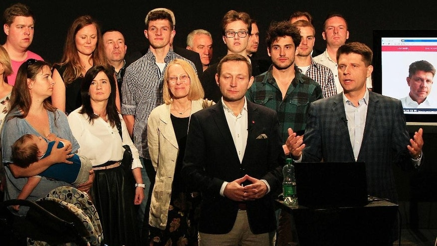 The leader of Poland's new political movement, ModernPL Association, economist Ryszard Petru, right, surrounded by followers at a news conference in Warsaw, Poland on Friday, June 26, 2015, talks about the transparent way of financing that his movement is seeking, via online donations from supporters. (AP Photo/Czarek Sokolowski)