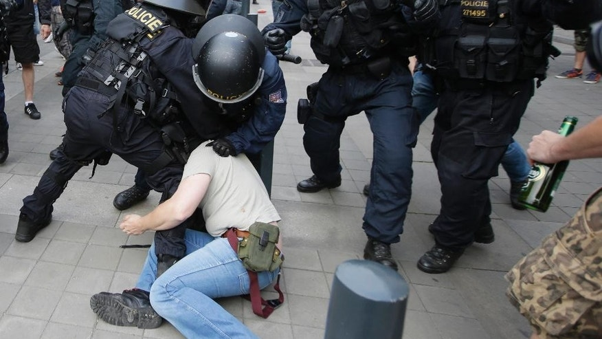 Riot policemen make an arrest during a far right demonstration in Brno, Czech Republic, Friday, June 26, 2015. Hundreds of far right protesters rallied against immigrants and Islam in the second largest Czech city of Brno while others gathered nearby in support of immigration. (AP Photo/Petr David Josek)