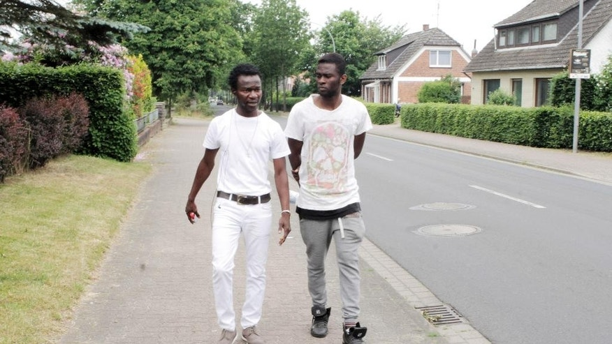 In this June 13, 2015 photo Jean Paul Apetey , left, and a fellow asylum seeker walk through the northern German village of Otter. Apetey enjoyed a well-organized, warm arrival in the north German state of Lower Saxony. (AP Photo/Dalton Bennett)