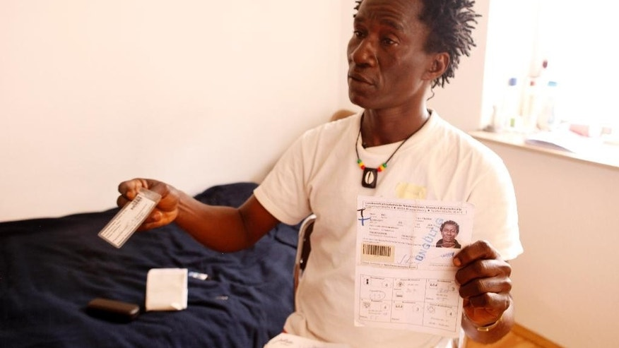 In this June 14, 2015 photo Hilarion Bie, who referred to himself as Hilarion Charlemagne at the beginning of his trip to Europe, shows his expired temporary residence card from his first shelter after arriving in an asylum-seeker shelter in Brietlingen, in the the northern German state of Lower Saxony. (AP Photo/Dalton Bennett)