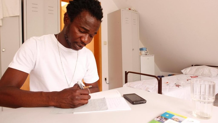 In this June 13, 2015 photo Jean Paul Apetey practices German in an asylum seeker shelter in Otter, northern Germany. Apetey enjoyed a well-organized, warm arrival in the north German state of Lower Saxony. (AP Photo/Dalton Bennett)